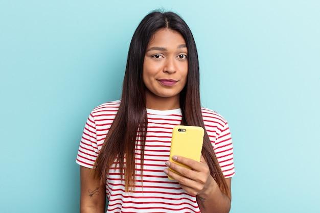 Jeune femme vénézuélienne tenant un téléphone portable isolé sur fond bleu confus, se sent dubitative et incertaine.