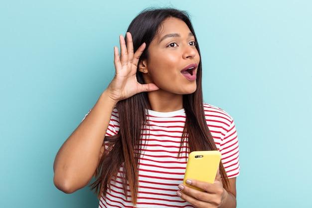 Jeune femme vénézuélienne tenant un téléphone portable isolé sur fond bleu essayant d'écouter un potin.
