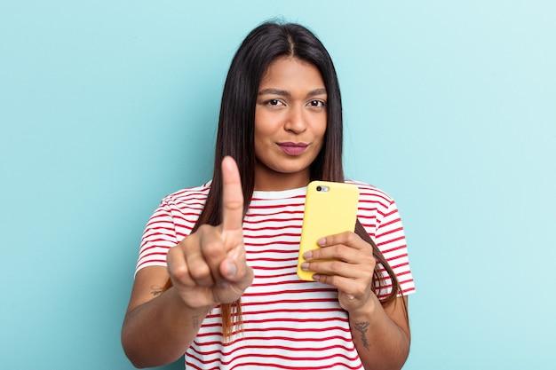 Jeune femme vénézuélienne tenant un téléphone portable isolé sur fond bleu montrant le numéro un avec le doigt.