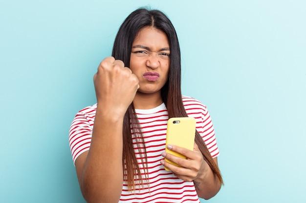 Jeune femme vénézuélienne tenant un téléphone portable isolé sur fond bleu montrant le poing à la caméra, expression faciale agressive.
