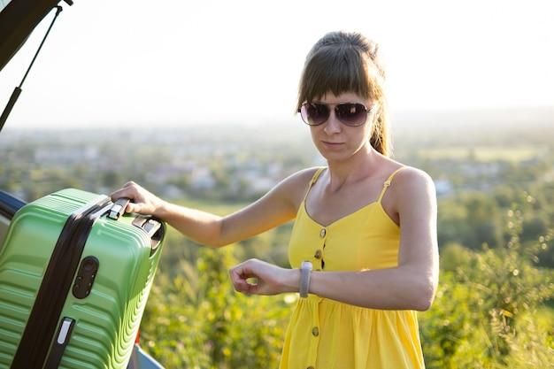 Jeune femme vérifiant l'heure lors de l'emballage de la valise dans le coffre de sa voiture. concept de voyage et de vacances.