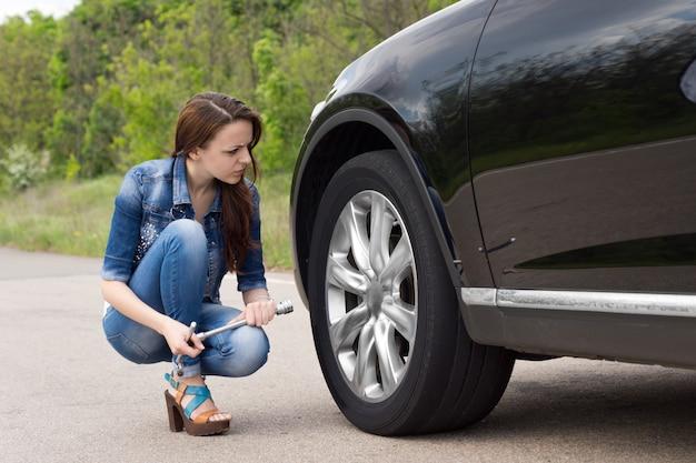 Jeune femme vérifiant un pneu crevé sur sa voiture