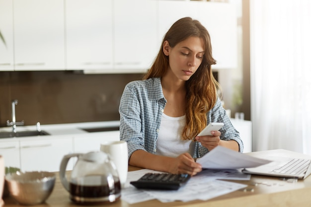 Jeune femme vérifiant son budget et faisant des impôts