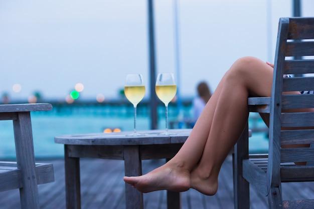 Jeune femme avec un verre de vin blanc au soir