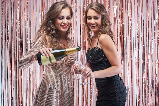 Jeune femme versant du champagne dans les verres.