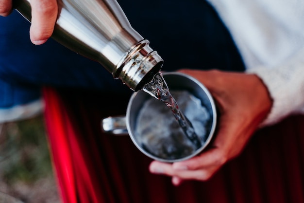 Jeune femme, verser, eau, dans, tasse métallique