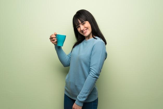 Jeune femme, sur, vert, mur, tenue, a, chaud, tasse café