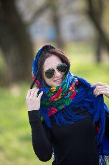 Jeune femme en veste cellulaire et lunettes de soleil noires