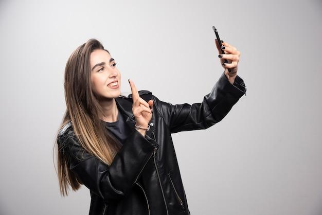 Jeune femme en veste de cuir prenant selfie avec son téléphone portable