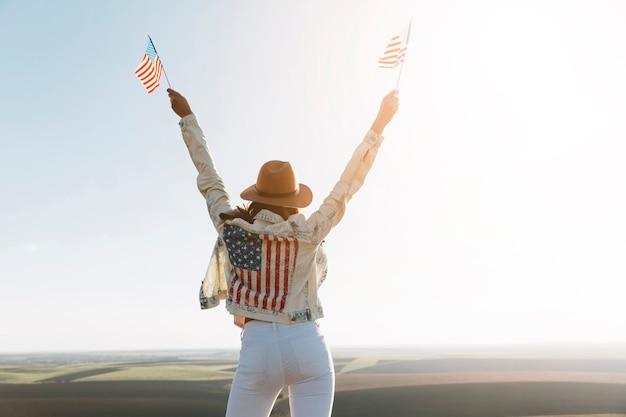 Jeune femme en veste de drapeau américain au sommet de la montagne