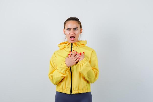 Jeune femme en veste jaune avec les mains sur la poitrine et à la perplexité, vue de face.