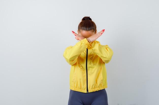 Jeune femme en veste jaune montrant un geste de refus et l'air agacée, vue de face.