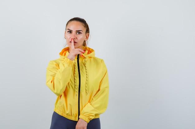 Jeune femme en veste jaune montrant un geste de silence et l'air confiant, vue de face.