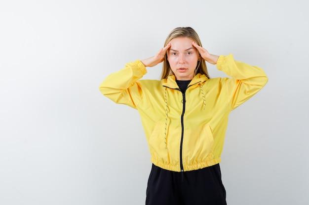 Jeune femme en veste jaune, pantalon tenant les mains sur la tête et regardant sombre, vue de face.