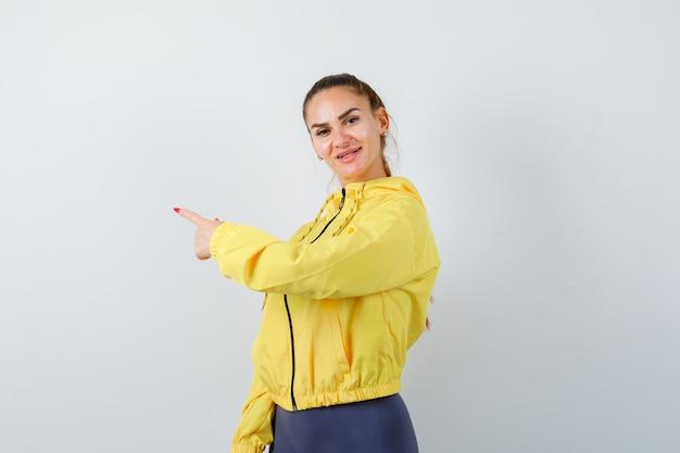 Jeune femme en veste jaune pointant de côté et à la gaieté, vue de face.