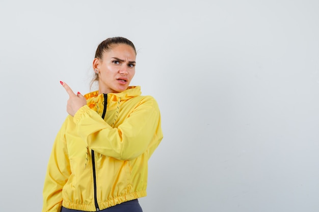 Jeune femme en veste jaune pointant vers le coin supérieur gauche et semblant insatisfaite, vue de face.