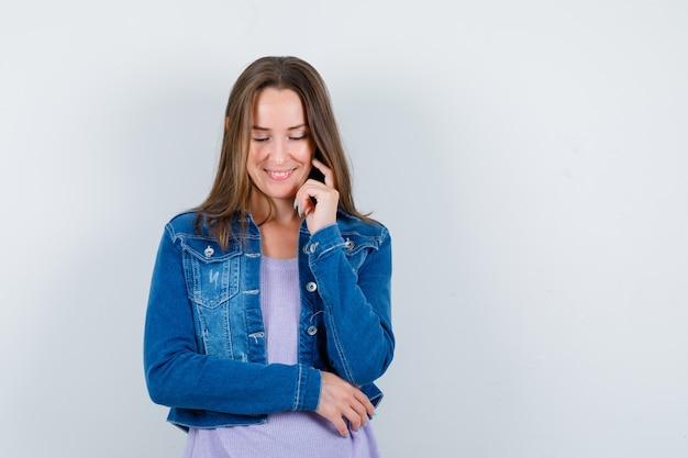 Jeune femme en veste en jean gardant le doigt sur la joue, regardant vers le bas et ayant honte, vue de face.