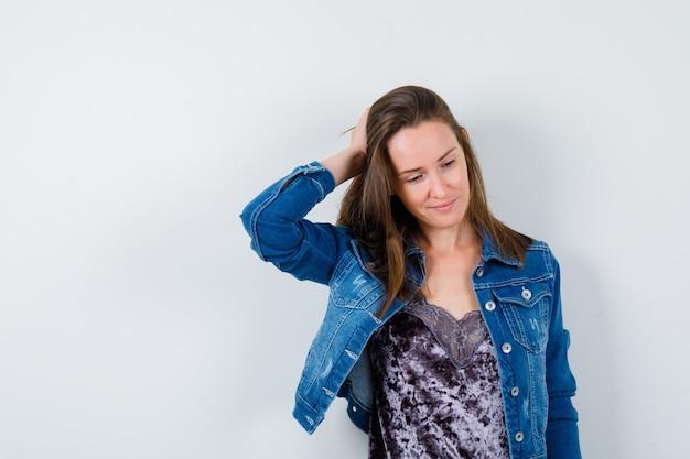 Jeune femme en veste en jean avec la main sur la tête, regardant vers le bas et à la recherche de rêve, vue de face.