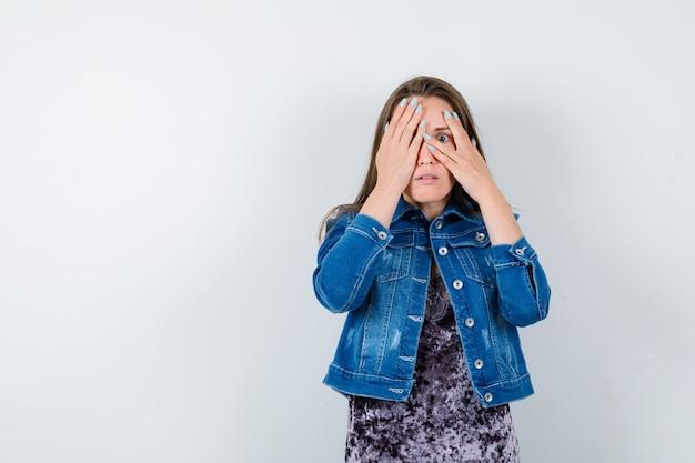 Jeune femme en veste en jean regardant à travers les doigts et semblant effrayée, vue de face.