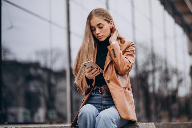 Jeune femme en veste marchant dans la ville