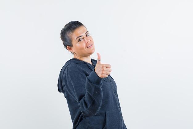 Jeune femme en veste montrant le pouce vers le haut et l'air assuré
