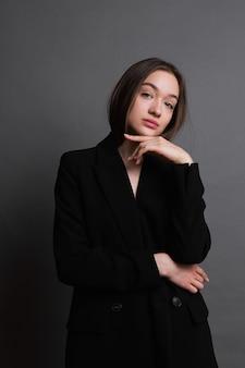 Jeune femme en veste noire sur fond gris foncé. fille avec émotions. fille qui pense