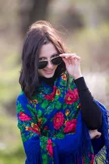 Jeune femme en veste noire et lunettes de soleil noires