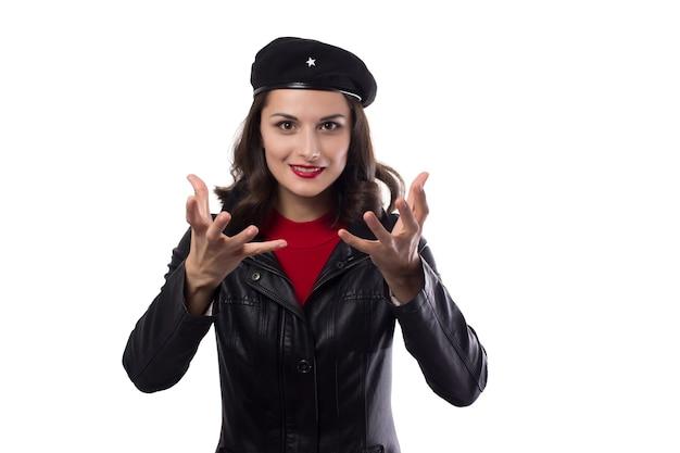Jeune femme veste noire, pull rouge et chapeau avec une référence à ernesto che guevara regardant à huis clos, montre de manière expressive ses mains et son sourire sur fond blanc