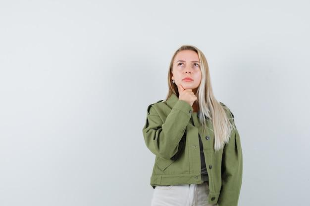 Jeune femme en veste, pantalon soutenant le menton à portée de main et à la recherche pensive, vue de face.