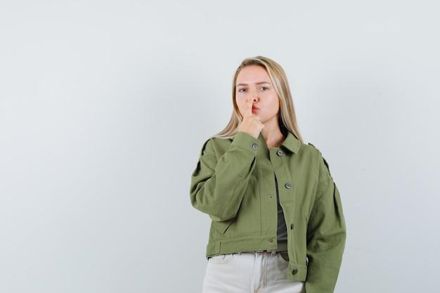 Jeune femme en veste, pantalon touchant son nez avec le doigt et à la belle vue de face.