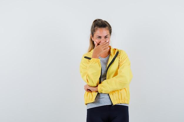 Jeune femme en veste, t-shirt tenant la main sur la bouche et à la jolly, vue de face.