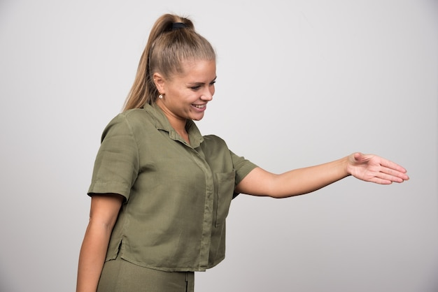 Jeune femme en veste verte offrant sa main à serrer.