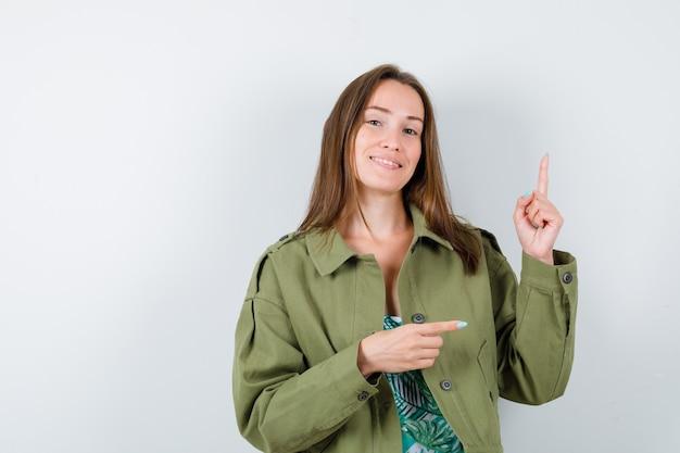 Jeune femme en veste verte pointant vers le haut et vers la droite et l'air gaie, vue de face.