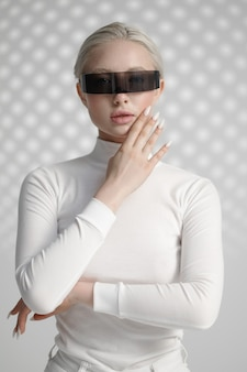 Jeune femme en vêtements blancs et lunettes futuristes, fond gris clair. personne de sexe féminin dans un style de réalité virtuelle, technologie future, concept de futurisme
