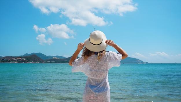 Jeune femme en vêtements blancs rafraîchissant à la plage de l'océan, chine