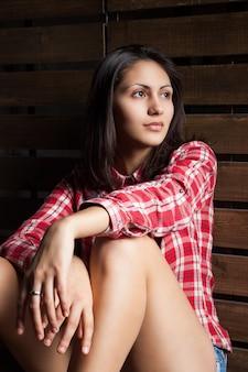 Jeune femme en vêtements de cow-boy sur bois