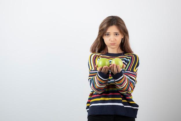 Jeune femme en vêtements décontractés debout avec des pommes vertes sur fond blanc.