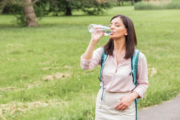 Jeune femme en vêtements décontractés l'eau potable provenant d'une bouteille en plastique dans le parc au printemps