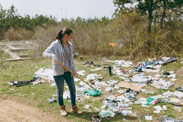 Jeune femme en vêtements décontractés et gants en latex pour le nettoyage à l'aide d'un râteau pour la collecte des ordures dans un parc jonché. problème de pollution de l'environnement. arrêtez les ordures de la nature, concept de protection de l'environnement.