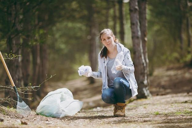 Jeune femme en vêtements décontractés, gants nettoyant les déchets dans des sacs poubelles dans un parc ou une forêt