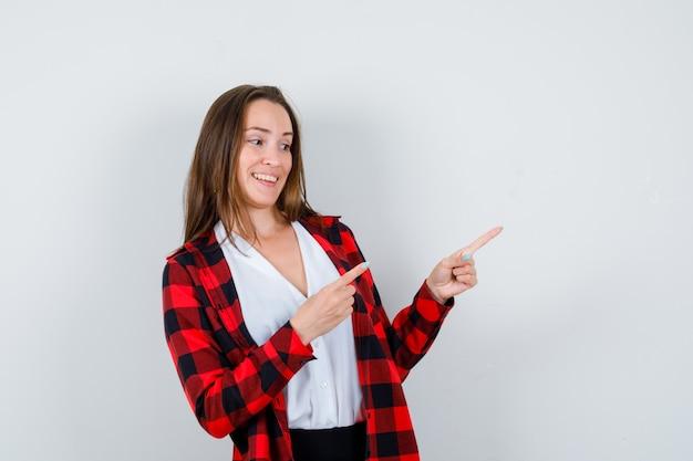 Jeune femme en vêtements décontractés pointant vers le coin supérieur droit et regardant jovial, vue de face.