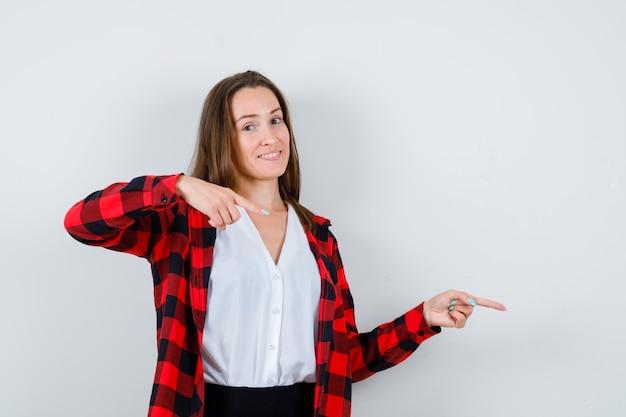 Jeune femme en vêtements décontractés pointant vers la droite et semblant indécise, vue de face.