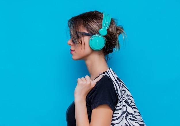 Jeune femme en vêtements et écouteurs zèbre sur fond bleu