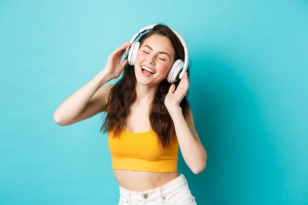 Jeune femme en vêtements d'été écoutant de la musique, portant des écouteurs et chantant la chanson préférée, dansant dans des écouteurs, debout sur fond bleu.