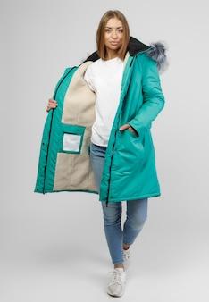 Jeune Femme En Vêtements D'hiver Sur Fond Blanc. Concept Photo Pour La Publicité D'une Doudoune. Photo Premium