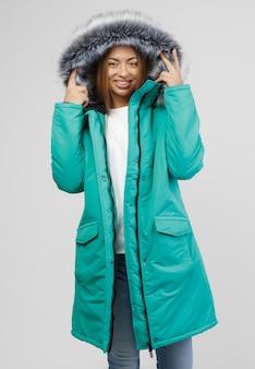 Jeune femme en vêtements d'hiver sur fond blanc. concept photo pour la publicité d'une doudoune.