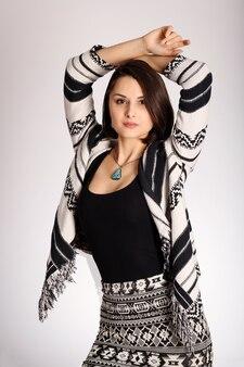 Jeune femme en vêtements imprimés aztèques posant sur fond blanc jolie femme fashion ethno