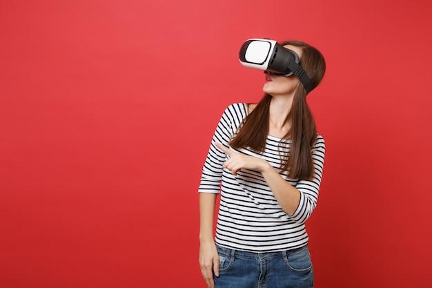 Jeune femme en vêtements à rayures décontractées lunettes de réalité virtuelle pointant l'index regardant de côté isolé sur fond de mur rouge vif. concept de mode de vie des émotions sincères des gens. maquette de l'espace de copie.