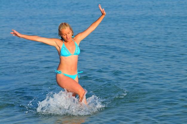 Jeune femme en vêtements de sport et baskets en cours d'exécution près du bord de mer encore et souriant sur une journée d'été ensoleillée. concept de bonheur, vacances et liberté