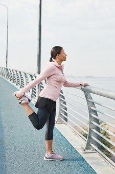 Jeune femme en vêtements de sport debout sur le pont faisant de l'exercice et regardant la belle mer